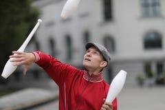 Een mens in een GLB jongleert met met clubs stock afbeelding