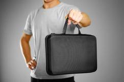 Een mens in een grijze t-shirt houdt een zwart geval op grijze bac stock foto