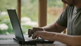 Een mens in een grijze T-shirt werkt in een ruimte met een venster overziend de tuin stock footage