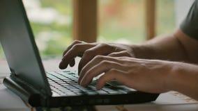 Een mens in een grijze T-shirt werkt in een ruimte met een venster overziend de tuin stock video