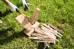 Een mens in handschoenen hakte hout met een bijl op het groene gras in de zomer royalty-vrije stock afbeelding