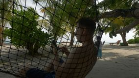Een mens in een hangmat met een mobiele telefoon op het strand, op de achtergrond een meisje die met zeepbels spelen stock video