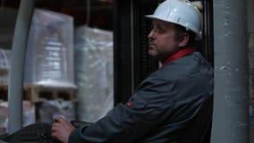 Een mens in een helm die een vorkheftruck langs het pakhuis berijden 4K langzame mo stock video