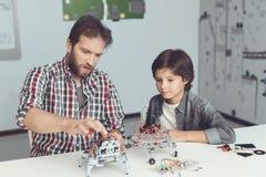Een mens helpt een jongen met een robotassemblage De jongen kijkt zorgvuldig aangezien een mens een robot verzamelt stock foto