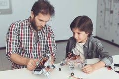 Een mens helpt een jongen met een robotassemblage De jongen kijkt zorgvuldig aangezien een mens een robot verzamelt stock afbeelding