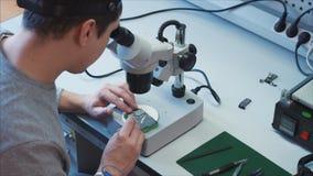 Een mens herstelt GSM bluetooth module Onderhoud van de hardware stock videobeelden