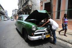 Een mens herstelt zorgvuldig zijn auto op een straat Stock Afbeelding
