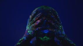 Een mens in het ultraviolette licht veegt het fluorescente poeder van zijn gezicht af Impotentie vóór het levensomstandigheden stock video