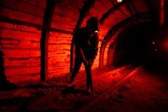 Een mens in het werkoverall en een helm met een jackhammer op zijn schouder bevindt zich op de sporen Silhouet in rood mijnwerker stock foto's