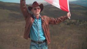 Een mens in een hoed en zonnebril, leerjasje en jeans die een Canadese vlag houden stock footage