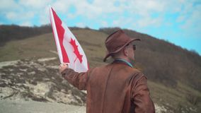 Een mens in een hoed en zonnebril, leerjasje en jeans die een Canadese vlag houden stock videobeelden
