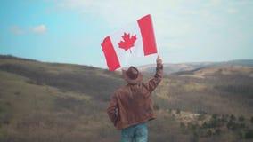 Een mens in een hoed en zonnebril, leerjasje en jeans die een Canadese vlag houden stock video