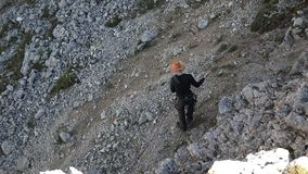 Een mens in een hoed onderaan de berg op een kabel stock footage