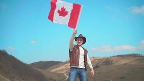 Een mens in een hoed, een vest en een leerjasje en jeans golft de Canadese vlag De vlag van Canada ontwikkelt zich in de wind stock footage