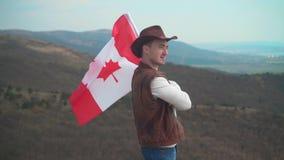 Een mens in een hoed, een vest en een leerjasje en jeans houdt een Canadese vlag De vlag van Canada ontwikkelt zich in de wind stock videobeelden