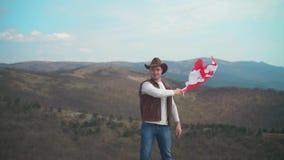 Een mens in een hoed, een vest en een leerjasje en jeans houdt een Canadese vlag De vlag van Canada ontwikkelt zich in de wind stock video