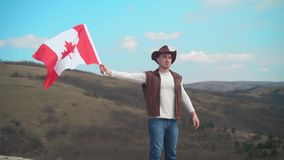 Een mens in een hoed, een vest en een leerjasje en jeans houdt een Canadese vlag De vlag van Canada ontwikkelt zich in de wind stock footage