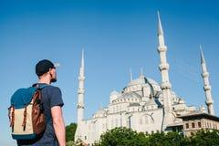 Een mens in een honkbal GLB met een rugzak naast de blauwe moskee is een beroemd gezicht in Istanboel Reis, toerisme stock afbeeldingen