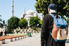 Een mens in een honkbal GLB met een rugzak naast de blauwe moskee is een beroemd gezicht in Istanboel Reis, toerisme stock foto's