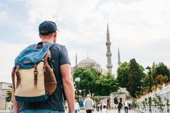 Een mens in een honkbal GLB met een rugzak naast de blauwe moskee is een beroemd gezicht in Istanboel Reis, toerisme stock fotografie