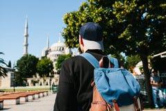 Een mens in een honkbal GLB met een rugzak naast de blauwe moskee is een beroemd gezicht in Istanboel Reis, toerisme stock afbeelding