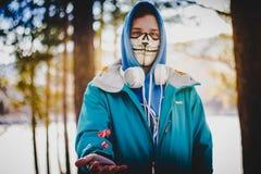 Een mens in hoofdtelefoons, een sweatshirt en een masker werpt dobbelt in de lucht stock foto
