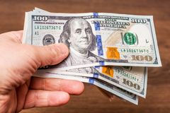Een mens houdt Amerikaanse dollars in zijn hand Het krijgen van een salaris Betaling voor purchase_ stock fotografie