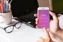 Een mens houdt Apple-iPhone 6 met Instagram-toepassing op het scherm App is grootste en populairste foto sociaal voorzien van een Royalty-vrije Stock Foto's