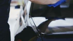 Een mens houdt een blauwe textiel, veegt en poetst een zwarte auto af op stock videobeelden