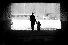 Een mens houdt de hand van een van de achtergrond meisjeswinter silhouet Stock Afbeelding