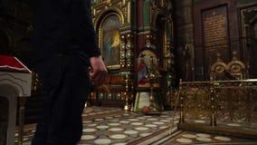 Een mens houdt in de handen van Kerkkaarsen Er zijn vele orthodoxe pictogrammen op de achtergrond stock video
