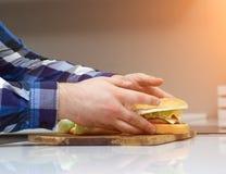 Een mens houdt in de handen van de keuken vettige sappige hamburgers, ongezonde kost, close-up, calorieën stock fotografie