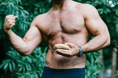 Een mens houdt een hamburger en toont een biceps Stock Foto