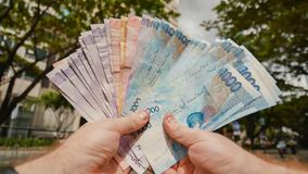 Een mens houdt Filippijnse geldrekeningen in zijn handen stock foto's