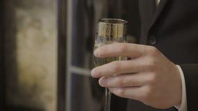 Een mens houdt een glas met een alcoholische drank stock video