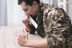 Een mens houdt een glas van alcohol in zijn hand en een foto van een militaire mens royalty-vrije stock fotografie