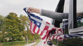 Een mens houdt een grote Amerikaanse vlag in zijn handen, port hem uit het venster van een bewegende auto langzame geanimeerde vi stock videobeelden