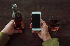 Een mens houdt een mobiele telefoon in zijn handen Daarna op de lijst is een glas en een fles whisky royalty-vrije stock foto