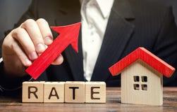 Een mens houdt een rode pijl boven het woordtarief en een blokhuis tegen Het concept het opheffen van rentevoeten op hypotheken E royalty-vrije stock fotografie