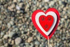 Een mens houdt een rood houten hart op een stok tegen de achtergrond van aard, hemel, stenen Het concept de Dag van Valentine Royalty-vrije Stock Foto's