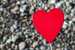 Een mens houdt een rood houten hart op een stok tegen de achtergrond van aard, hemel, stenen Het concept de Dag van Valentine Stock Foto's