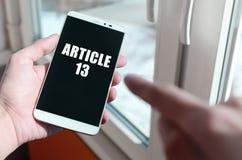 Een mens houdt een smartphone met Artikel 13 inschrijving stock fotografie
