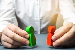 Een mens houdt in zijn handen de rode en groene cijfers die van mensen elkaar onder ogen zien Het onderzoek naar een compromis, b royalty-vrije stock afbeelding