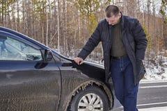 Een mens inspecteert de bevroren auto Royalty-vrije Stock Fotografie