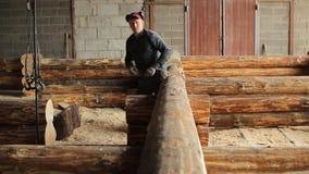 Een mens inspecteert straalhuis op de nauwkeurigheid van de installatie Half gebouwd blokhuis stock video