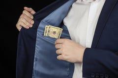Een mens in een jasje in een borstzak houdt dollars, zwarte zaken als achtergrond stock foto