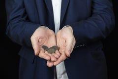 Een mens in een jasje houdt muntstukken op de palmen van zijn handen royalty-vrije stock foto