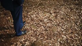 Een mens in een jasje loopt door het hout stock videobeelden