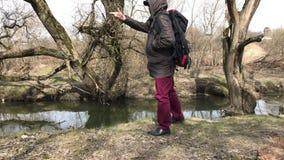 Een mens in een jasje met een kap loopt langs de rivierbank Heft de glasfles op, werpt het aan de kant, en gaat  Spr stock footage