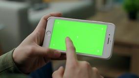 Een mens kiest een karakter op een smartphone met het groen scherm in de woonkamer stock video